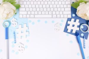 white desk with light blue and dark blue props like a keyboard, white flowers, markers, confetti, a notebook
